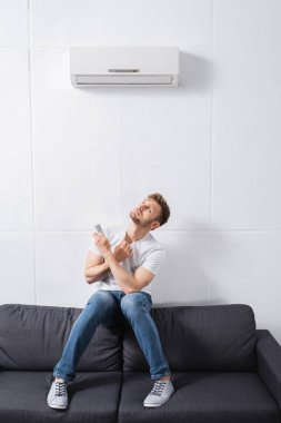 Confused man holding remote controller and suffering from heat with broken air conditioner at home stock vector