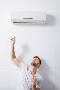 Sad man feeling uncomfortable with broken air conditioner at home during summer heat stock vector