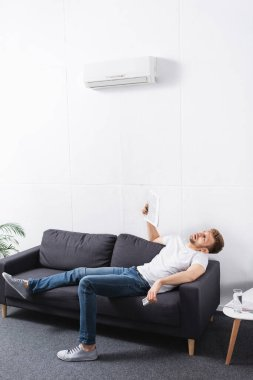Exhausted man suffering from heat while using newspaper as hand fan at home with broken air conditioner stock vector