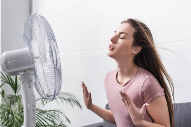 Beautiful girl feeling comfortable with electric fan during summer heat stock vector