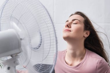 Attractive positive girl feeling comfortable with electric fan at home during summer heat stock vector
