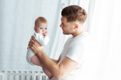 Photo young father looking at adorable baby boy while holding him in bedroom