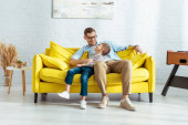 Photo cheerful father and son talking while sitting on yellow sofa