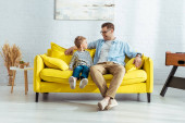 happy father and son talking while sitting on yellow sofa
