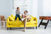 šťastný otec a syn jíst popcorn, zatímco sedí na žluté pohovce