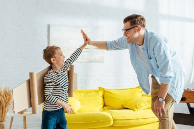 Cute boy with cardboard plane wings on back giving high five to father stock vector