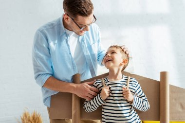 Happy father touching head of cheerful son with cardboard plane wings on back stock vector