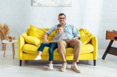 Happy father and son looking at camera while sitting on yellow sofa stock vector