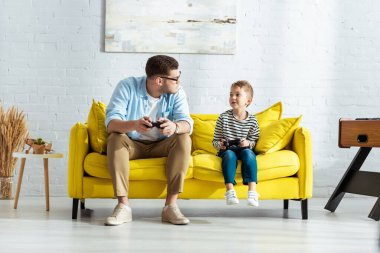 KYIV, UKRAINE - JUNE 9, 2020: young father and adorable son looking at each other while sitting on yellow sofa with joysticks stock vector