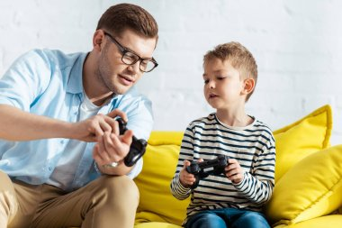 KYIV, UKRAINE - JUNE 9, 2020: young father showing joystick to attentive son stock vector