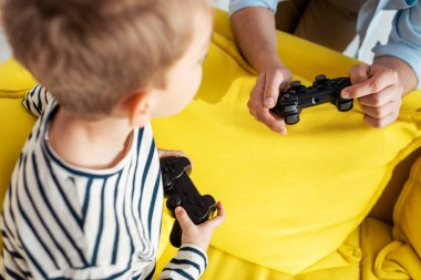 KYIV, UKRAINE - JUNE 9, 2020: cropped view of man showing joystick to attentive son stock vector