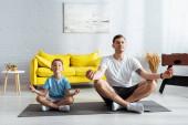 apa és fia ül lótusz pózol fitness mat csukott szemmel