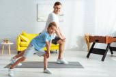 šťastný otec a syn dělá výpady při cvičení doma