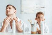 selektivní zaměření seriózní muž dotýká tvář blízko usmívající se syn v koupelně