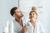 selektivní zaměření mladého otce dotýkající se vlasů veselého syna v blízkosti toaletní potřeby v koupelně