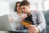 Válogatott fókusz a férfi kezében hitelkártya használata közben laptop közelében barátnője otthon