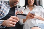 Szelektív fókusz pozitív férfi gazdaság hitelkártya használata közben okostelefon közelében nő