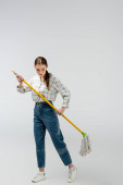 attraktives Mädchen posiert wie eine Marionette isoliert auf grau