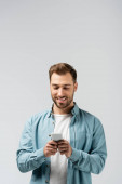 Photo smiling young man using smartphone isolated on grey