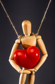 close up view of wooden marionette on strings with red heart isolated on black