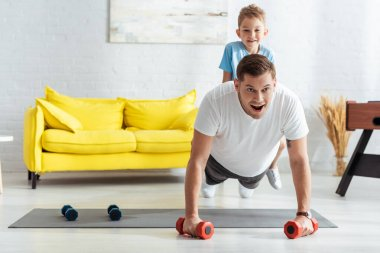Young man doing push ups with dumbbells while son sitting on his back stock vector