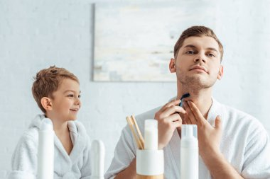 Selective focus of young man shaving neck near smiling son in bathroom stock vector