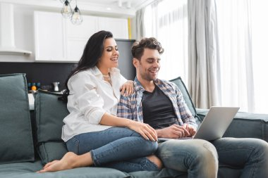 Smiling woman sitting near handsome boyfriend using laptop on couch at home stock vector