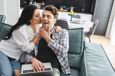 Selective focus of attractive girl kissing cheerful boyfriend using laptop on couch stock vector