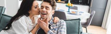 Panoramic crop of beautiful woman kissing smiling boyfriend in living room stock vector
