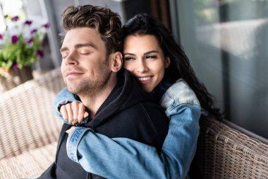 Beautiful smiling girl hugging handsome boyfriend on wicker sofa on terrace stock vector