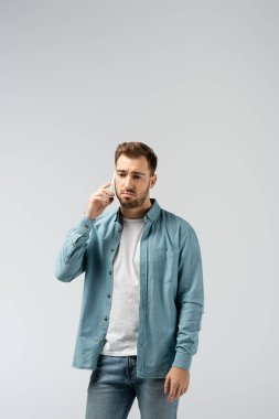 sad young man talking on smartphone isolated on grey