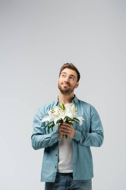 Dreamy young man with floral bouquet isolated on grey stock vector