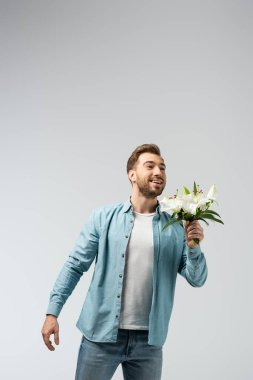 Happy young man with floral bouquet isolated on grey stock vector