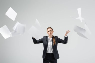 Displeased businesswoman in suit throwing papers in air isolated on grey stock vector