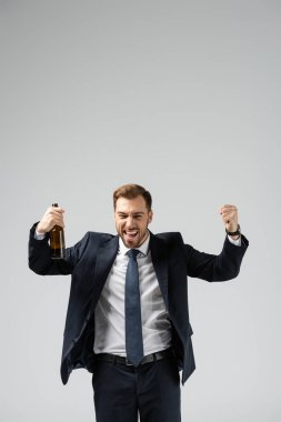 Handsome businessman in suit rejoicing with beer isolated on grey stock vector