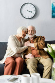 selective focus of happy senior couple sitting on sofa and holding hands