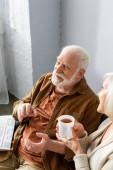 vysoký úhel pohledu na usmívající se starší muž mluví s manželkou drží šálek čaje