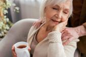 oříznutý pohled na muže dotýkajícího se ramene šťastné starší ženy držící šálek čaje se zavřenýma očima