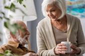 szelektív összpontosítás mosolygós idősebb nő kezében csésze teát, miközben beszél a férjjel