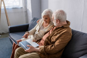 glückliches Seniorenpaar sitzt auf Sofa und benutzt Laptop mit leerem Bildschirm