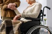 Ausgeschnittene Ansicht eines älteren Mannes, der behinderte, kranke Frau im Rollstuhl an der Hand hält