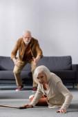 selektivní zaměření staršího muže spěchající na pomoc manželce ležící na podlaze v blízkosti vycházkové hole