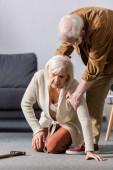 senior muž pomáhá vstát padlé manželky sedí na podlaze