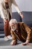 oříznutý pohled na ženu pomáhá padlý starší manžel vstát z podlahy