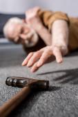 selektivní zaměření bezmocného staršího muže ležícího na podlaze a snažícího se dostat vycházkovou hůl
