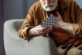 selektivní zaměření staršího muže dotýkání hrudníku a držení pilulek při špatném pocitu