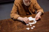 vysoký úhel pohledu na seniora muž hraje puzzle jako demence terapie