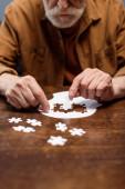 ostříhaný pohled na staršího muže hrající puzzle pro rehabilitaci demence
