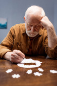 selective focus of senior man collecting jigsaw puzzle as dementia therapy