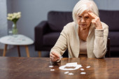 thoughtful senior woman collecting jigsaw puzzle as dementia therapy
